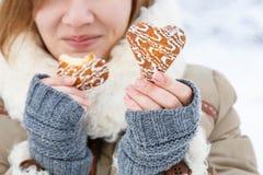 La jeune femme dans le manteau d'hiver et les mitaines grises tricotées tiennent le beautif Image stock