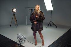 La jeune femme dans le manteau de fourrure est tirée dans le studio images libres de droits