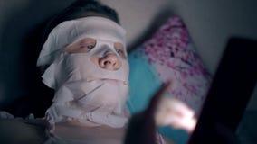 La jeune femme dans le masque blanc de feuille se trouve sur l'oreiller fleuri bleu banque de vidéos