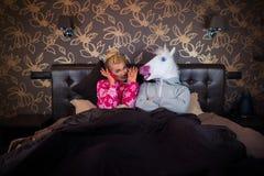 La jeune femme dans le pyjama s'assied sur le lit photos stock