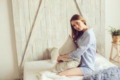 La jeune femme dans le pyjama se réveillent le matin dans la chambre à coucher scandinave confortable et le mensonge sur le lit a image stock