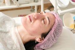 La jeune femme dans le salon de beaut? fait la peau hydratant la proc?dure apr?s l'?pluchage d'ultrason images stock