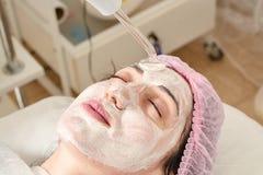 La jeune femme dans le salon de beauté fait rajeunir, modifiant la tonalité la procédure darsonval sur le visage photos stock