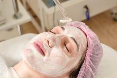 La jeune femme dans le salon de beauté fait rajeunir, modifiant la tonalité la procédure darsonval sur le visage image stock
