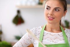 La jeune femme dans le tablier vert fait cuire dans la cuisine Femme au foyer pensant au menu tout en tenant une cuillère en bois Photos libres de droits