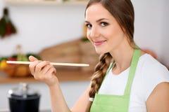 La jeune femme dans le tablier vert fait cuire dans une cuisine La femme au foyer goûte la soupe par la cuillère en bois Image libre de droits