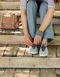 La jeune femme dans les blues-jean et des espadrilles rayées s'assied sur le vieux woode Photos stock