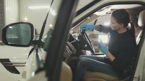 La jeune femme dans les gants bleus nettoie l'intérieur de la voiture pour SUV de luxe photo libre de droits