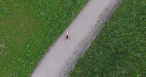 La jeune femme dans la robe mettent en marche le chemin de gravier en parc Bourdon se levant vers le haut du tir aérien banque de vidéos