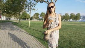 La jeune femme dans la robe retire du téléphone intelligent de sac à main et commence des entretiens banque de vidéos