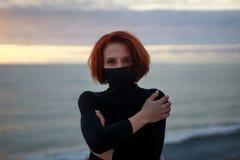 La jeune femme dans un chandail noir avec un regard mystérieux est contre le coucher du soleil image stock