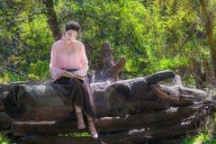 La jeune femme dans un style de Boho lit dans la retraite dans les avants Image libre de droits