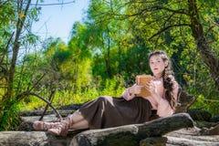 La jeune femme dans un style de Boho lit dans la retraite dans les avants Photographie stock
