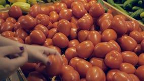 La jeune femme dans une épicerie examine des tomates banque de vidéos