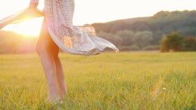 La jeune femme dans une torsion légère de robe, la jupe clignote à travers du coucher de soleil banque de vidéos