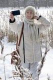 La jeune femme dans une veste blanche fait un selfie sur la côte du lac de forêt d'hiver photos libres de droits