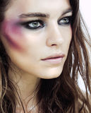 La jeune femme de beauté avec le maquillage aiment le menhaden sur le visage Image stock