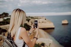 La jeune femme de beauté prennent la photo au téléphone du beau paysage d'océan avec l'eau et la falaise au Portugal concept de c photographie stock