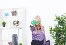 La jeune femme de blounde au bureau tient grand une clé verte Images stock