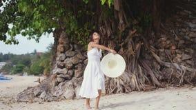 La jeune femme de brune avec de longs cheveux dans les drees et le chapeau blancs montre du doigt pour la suivre, marchant sur la clips vidéos