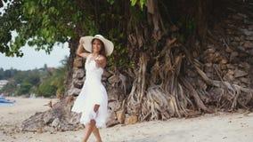 La jeune femme de brune avec de longs cheveux dans les drees et le chapeau blancs montre du doigt pour la suivre sur la plage tro Images libres de droits