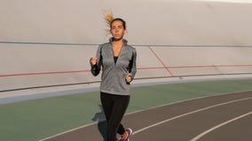 La jeune femme de brune court pendant le matin sur la voie de sport photo libre de droits