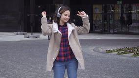 La jeune femme de brune dans des écouteurs danse clips vidéos