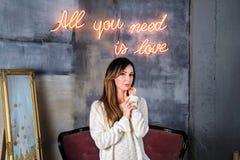 La jeune femme de brune dans un chandail confortable se tenant devant tous que vous avez besoin est enseigne au néon d'amour sur  Photo stock