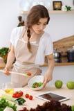 La jeune femme de brune est faisante cuire et goûtante la salade fraîche dans la cuisine Femme au foyer tenant la cuillère en boi Photos libres de droits