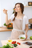 La jeune femme de brune est faisante cuire et goûtante la salade fraîche dans la cuisine Femme au foyer tenant la cuillère en boi Photographie stock