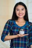 La jeune femme de brune faisant face à l'appareil-photo, tenant le pot en verre avec des pièces de monnaie à l'intérieur, lecture photo libre de droits