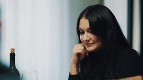 La jeune femme de brune souriant et s'accroche verre de vin à la table de dîner banque de vidéos