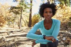 La jeune femme de couleur dans une forêt vérifiant le smartwatch regarde loin Photographie stock libre de droits