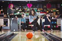La jeune femme de couleur joue au bowling Photo stock