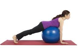 La jeune femme de forme physique faisant l'équilibrage s'exerce sur la boule de pilates Image libre de droits