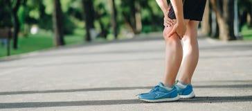 La jeune femme de forme physique tenant sa blessure à la jambe de sports, muscle douloureux pendant la formation image libre de droits