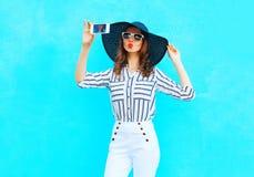 La jeune femme de mode prend une photo sur un smartphone utilisant un chapeau d'été de paille, pantalon blanc au-dessus de bleu c Photographie stock libre de droits