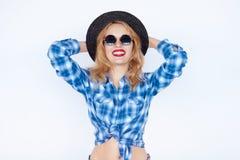 La jeune femme de mode s'est habillée dans une chemise bleue de plaid et un chapeau noir photos libres de droits