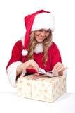 La jeune femme de Noël ouvre des présents de Noël Image stock