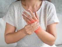 La jeune femme de plan rapproché s'asseyant sur le sofa tient sa blessure de main de poignet photo stock