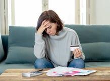 La jeune femme de renversement a soumis à une contrainte au sujet des dettes de carte de crédit et des finances de comptabilité n images stock