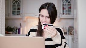 La jeune femme de sourire attirante emploie la carte de crédit en plastique faisant des emplettes en ligne avec l'ordinateur port banque de vidéos