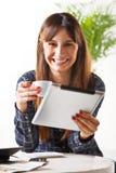 La jeune femme de sourire avec du café et soumettent un comprimé images libres de droits