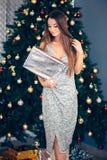 La jeune femme de sourire avec le cadeau de Noël enferment dans une boîte près de l'arbre de Noël Vacances, célébration et les ge images stock