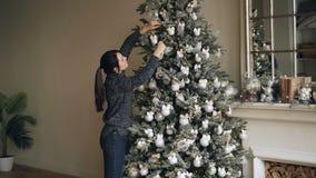 La jeune femme de sourire décore l'arbre de Noël vert avec de belles boules créant la conception authentique étant prête pour clips vidéos