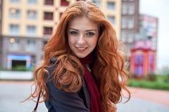 La jeune femme de sourire dans le manteau et avec les cheveux rouges longtemps débordants pose photos stock