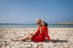 La jeune femme de sourire dans la robe rouge élégante s'assied dessus sur la plage photos stock