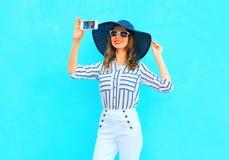 La jeune femme de sourire de mode prend une photo sur un smartphone utilisant un chapeau d'été de paille, pantalon blanc au-dessu Photographie stock