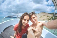 La jeune femme de sourire heureuse avec l'ami ou le mari font le selfie dans le bateau blanc Photographie stock libre de droits