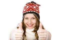 La jeune femme de sourire heureuse avec le capuchon affiche des pouces vers le haut Photo stock